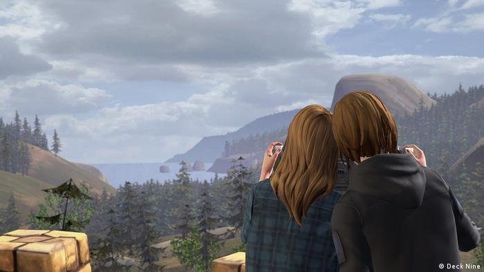 "Screenshot from the videogame Life is Strange: Before the Storm"" Two women arm in arm with a sea view before the mountains. (Deck Nine)"
