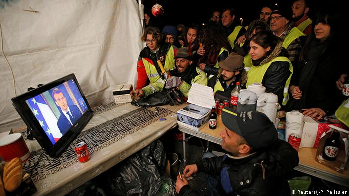 Protesters wearing yellow vests watch Emmanuel Macron on a TV screen in a motorway toll booth