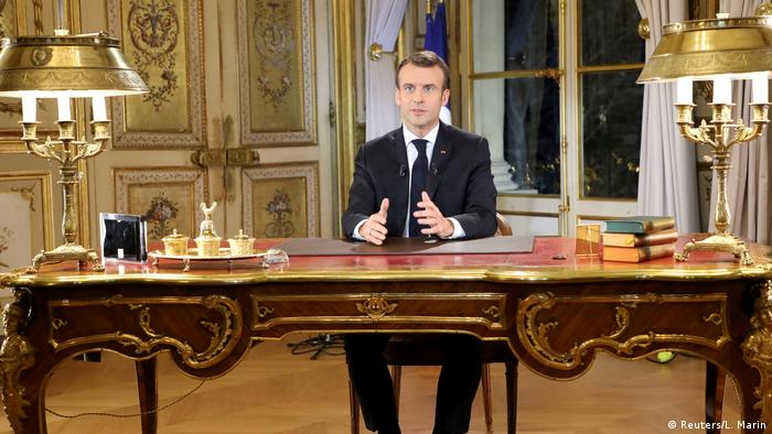 Macron sits at an elaborate desk and holds out his hands as he gives a televised address (Reuters/L. Marin)