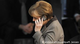 Ангела Меркель говорит по сотовому телефону