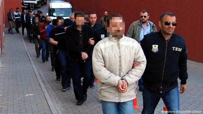 Männer in Handeschellen werden von türkischen Polizisten abgeführt (picture-alliance/dpa/Depo)