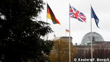 The flags of Germany, Britain and the EU wave on a winter's day in Berlin