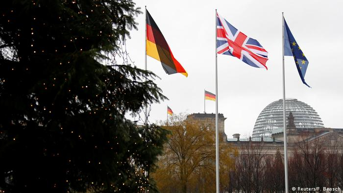 German, British and EU flags flutter in front of the Reichstag building in Berlin