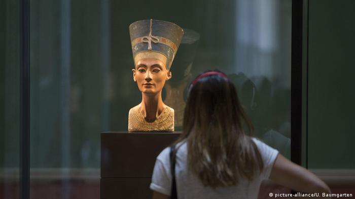 A museum visitor looks at the bust of Nefertiti in Berlin's Neues Museum