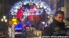 A police officer and ambulances at the scene of the Strasbourg Christmas market attack (picture-alliance/dpa/aptn)