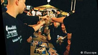 A group of young people cheers their glasses together at a table