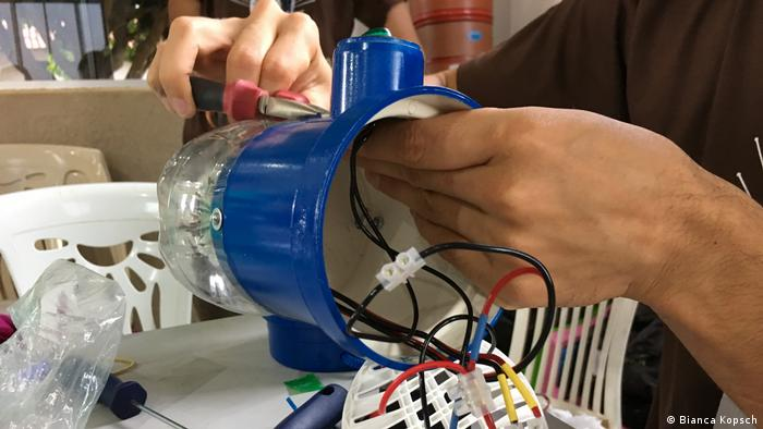Litro de Luz solar power lamp being constructed from a bottle in Brazil