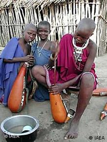 Mariam Kapurwa, 16, left, washes milk containers in Sokoine Village, Tanzania. Tsetse eradication would allow herdspeople to own more productive livestock.