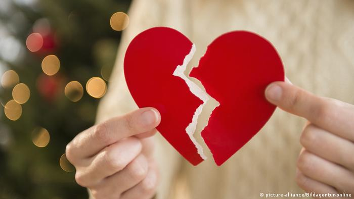 A woman holds the symbol of a heart broken in two in front of a Christmas tree