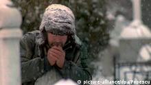 Ein Obdachloser haucht in seine Hände, um sich am 30.12.1996 bei starkem Schneefall auf einem Friedhof in Bukarest ein wenig aufzuwärmen. In Rumänien fielen in den vergangenen Tagen rund 20 Obdachlose der Kälte zum Opfer.  
