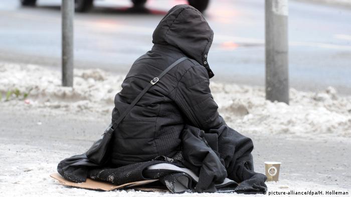 Beggar sitting on snowy sidewalk