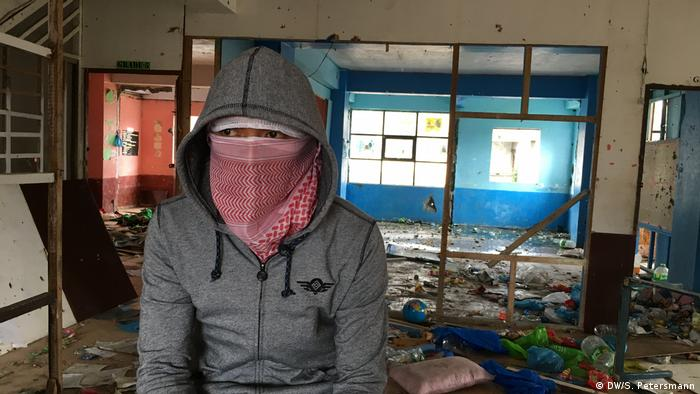 Abdul sits in a ruined classroom, his face covered