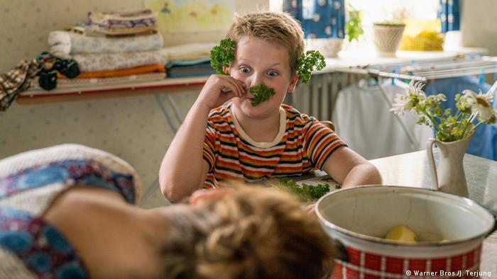 Filmstill aus Der Junge muss an die frische Luft, ein Junge mit Petersilie im Geschicht blickt mit aufgerissenen Augen eine Frau an, die den Kopf auf eine Tischplatte gelegt hat (Warner Bros./J. Terjung )