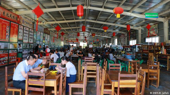 People sitting in a restaurant at the Chinese food market in Lusaka (DW/A-B. Jalloh)