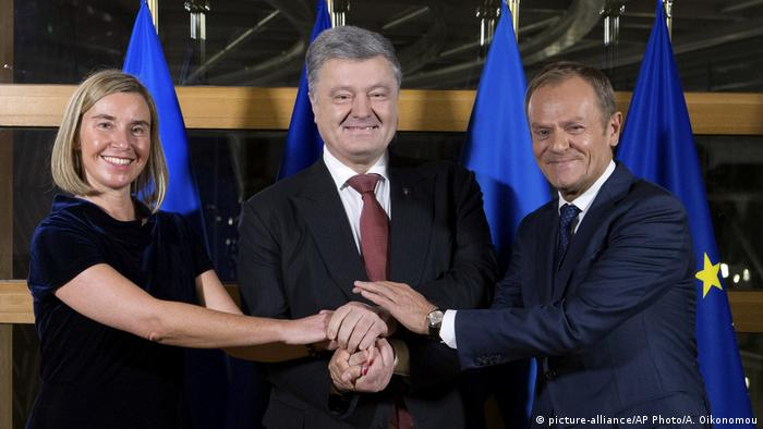 Ukrainian President Petro Poroshenko joins hands with European Union foreign policy chief Federica Mogherini and European Council President Donald Tusk prior to a meeting at the Europa building in Brussels, Wednesday, Dec. 12, 2018