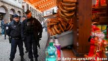 Police officers stroll past a Christmas market stall (Getty Images/AFP/S. Bozon)