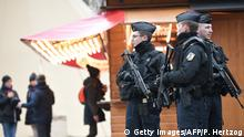 Armed policemen stand guard at Strasbourg's Christmas market, on its reopening day, on December 14, 2018, one day after French police shot dead the gunman who killed three people there. (Photo by PATRICK HERTZOG / AFP) (Photo credit should read PATRICK HERTZOG/AFP/Getty Images)