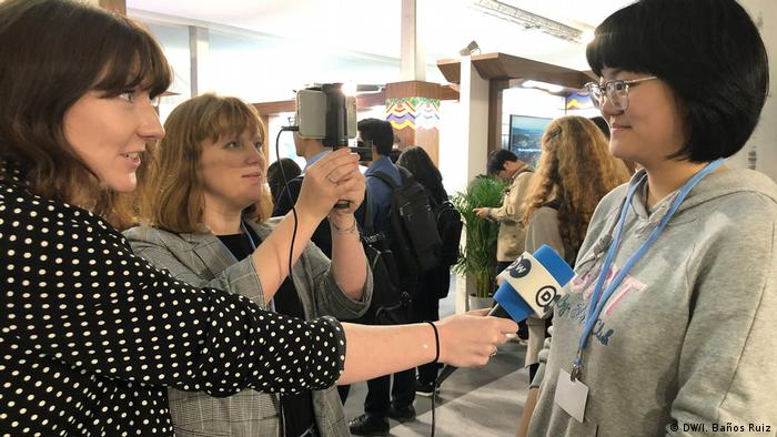 DW Global Ideas reporters Jennifer Collins and Louise Osborne interviewing a young participant from China at the COP24 climate conference.