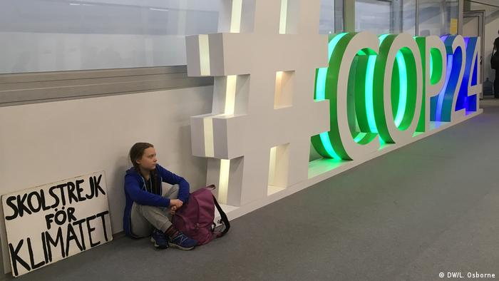Greta Thunberg sits next to the COP24 sign with a sign that says, school strike for climate.