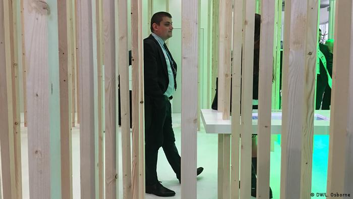 A man stands among the trees in the Polish pavilion at the COP24 climate conference.