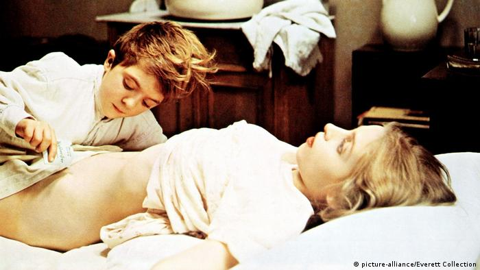 Film still from 'The Tin Drum': actors David Bennent and Katharina Thalbach in bed, her dress is lifted up, revealing a part of her body (picture-alliance/Everett Collection)