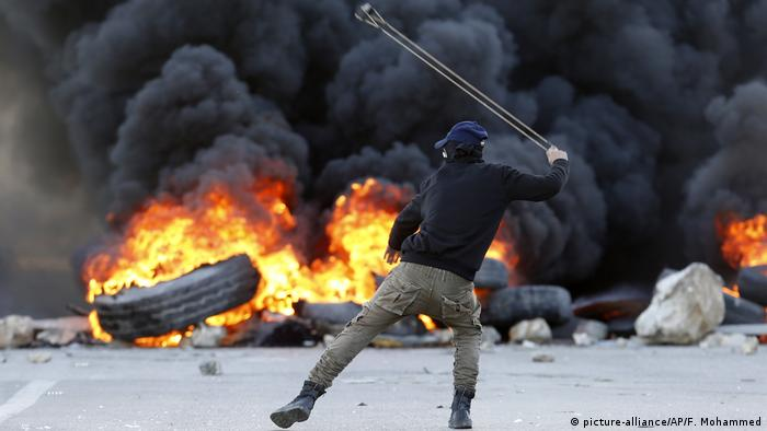 A Palestinian hurls stones at Israeli forces in the West Bank (picture-alliance/AP/F. Mohammed)