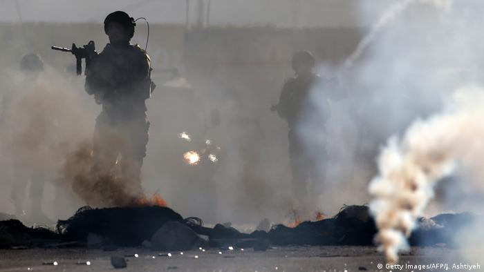 Soldiers walk with raised rifles through smoke from burning tires (Getty Images/AFP/J. Ashtiyeh)