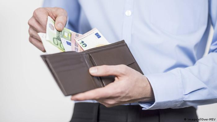 Man holds money out from wallet