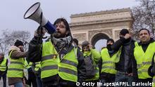 Yellow vest protester shouts into a loudspeaker (Getty Images/AFP/L. Barioulet)