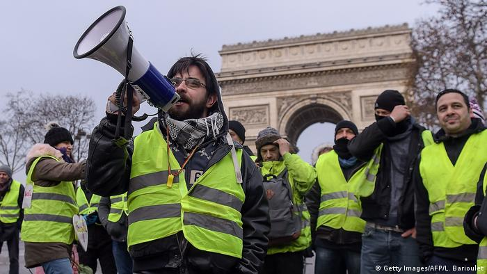 A yellow vest protester shouts into a megaphone