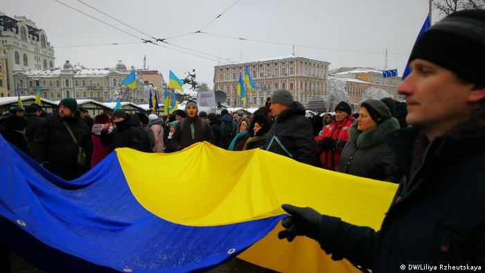 Люди несут флаг Украины