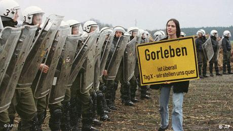 An anti-nuclear activist with sign walks past line of riot police in Gorleben, 1997 (AP)