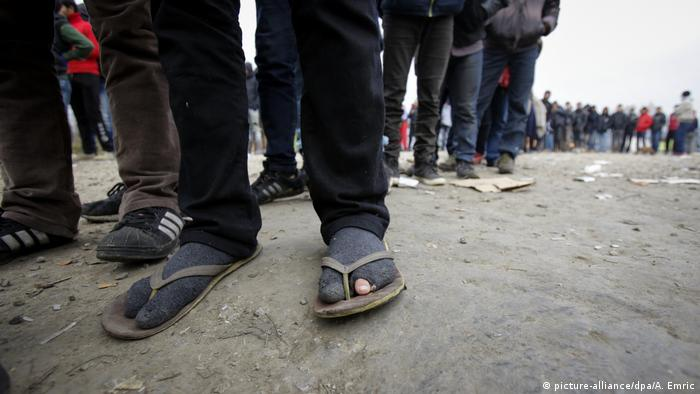 The feet of people waiting to cross into Croatia