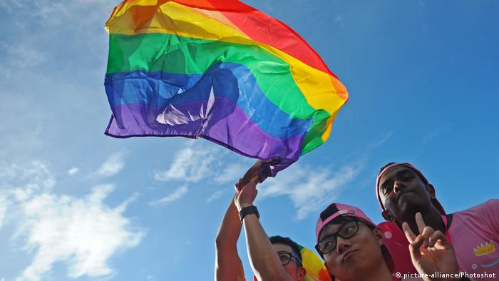 Gay rights supporters wave a rainbow flag in the air