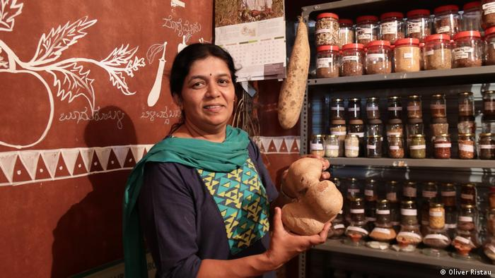 A woman stands in front of a shelf full of seeds at the Sahaja Organics cooperative in Bangalore, India.