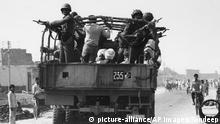 Indian army soldiers stand on their truck with their rifles as a group of Sikhs is brought to a nearby camp in New Delhi, Nov. 8, 1984, in an effort to give them maximum security and shelter. (AP Photo/Sondeep) |