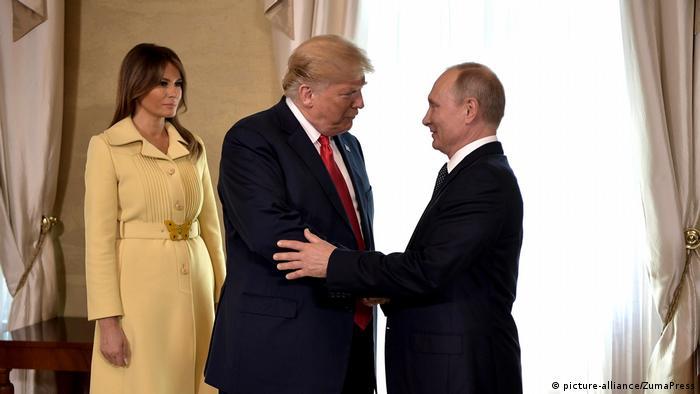 Трамп и Путин пожимают друг други руки во время встречи в Хельсинки в июле 2018 года, на заднем плане - Мелания Трамп