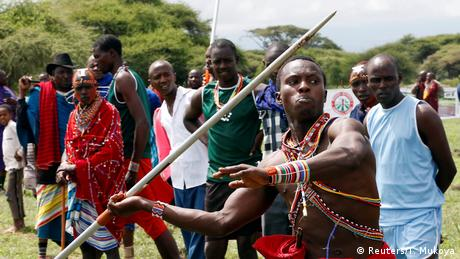 A Maasai moron wearing traditonal beads across his torso prepares to launch a javelin while other people look on. (Reuters/T. Mukoya)