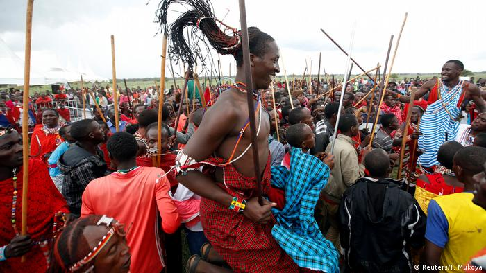 A Maasai man is elevated above the crowd as he jumps (Reuters/T. Mukoya)