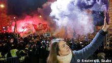 Anna Donath, vice president of the Momentum Movement opposition party, holds a flare during a protest in Budapest against the new 'slave law' (Reuters/B. Szabo)