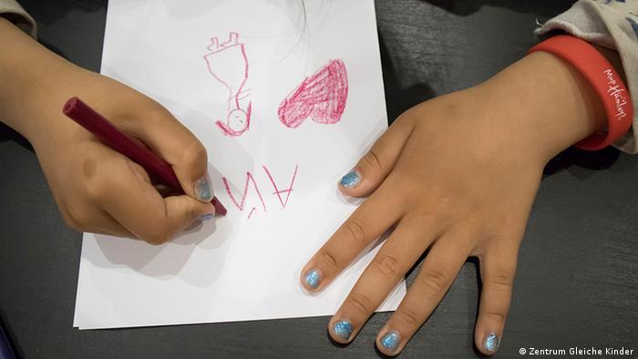 Ребенок рисует и пишет на листке бумаги