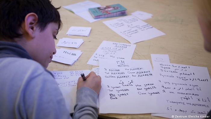 Мальчик пишет на листках бумаги