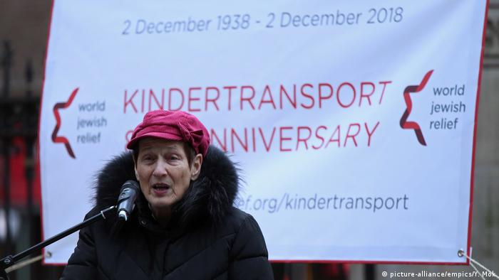 Survivor from the Kindertransport Ruth Barnett speaks at an anniversary event in London , wearing a pink cap and standing in front of a banner.