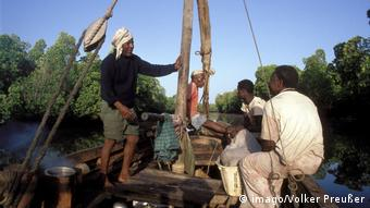 Fishermen sitting in the prow of a wooden boat