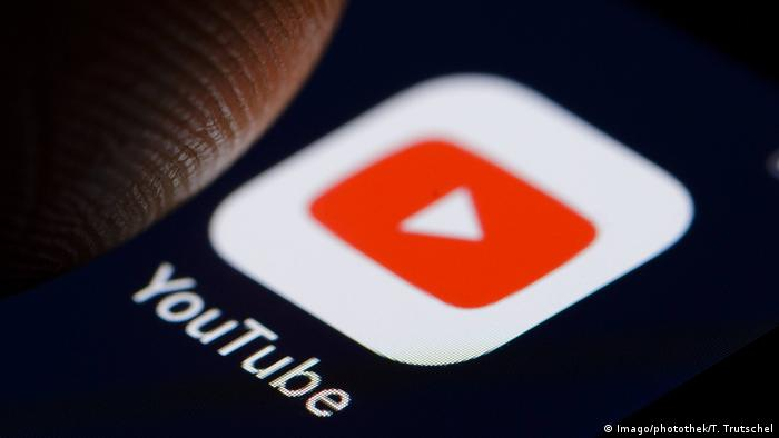 A thumb over a YouTube app icon on a phone