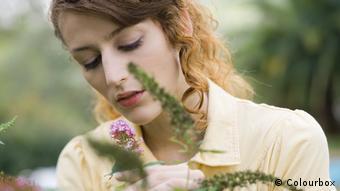 Девушка держит в руках цветок