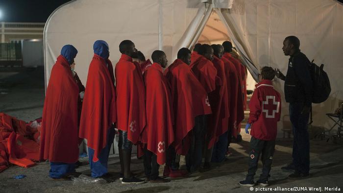 Los refugiados, envueltos en mantas rojas, son atendidos por la Cruz Roja después de llegar al puerto de Málaga. 246 migrantes fueron rescatados por el buque de rescate Guadamar Polimnia. Más y más africanos están evitando la ruta a Libia, tomando ahora la ruta del Mediterráneo occidental desde Argelia o Marruecos.