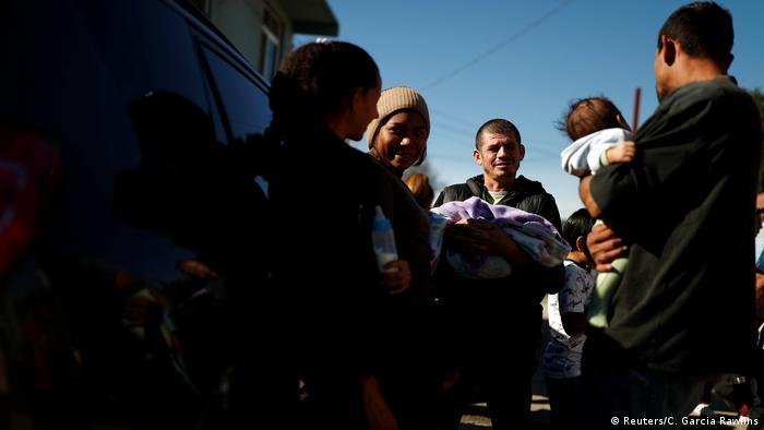 Migrante hondurenho segura seu filho recém-nascido em Tijuana, no México