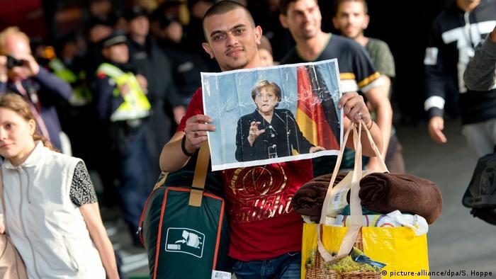 Pessoa segura foto de Merkel