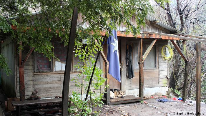 A wooden house with a Mapuche flag in front of it